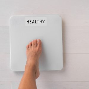 one foot steps on a scale that says healthy instead of a number