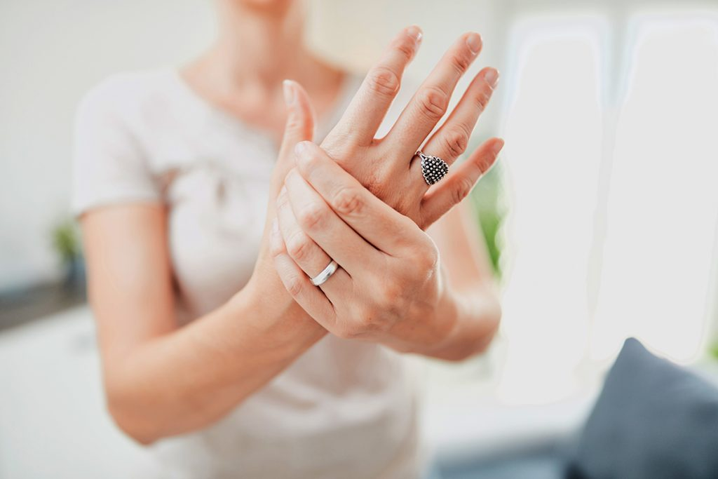 Woman clenches one hand with another, as if in pain